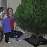 Adela and Mommy putting lights on the Christmas tree