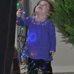 Adela watching Mommy with the Christmas tree lights